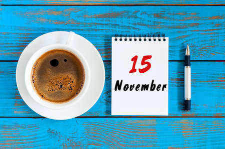 November 15th. Day 15 of month, hot coffee cup with calendar on accauntant workplace background. Autumn time. Empty space for text. Stock Photo