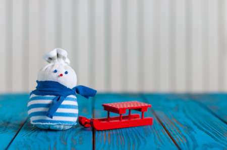Red sled and little handmade snowman on light wooden background. Xmas card with empty space for text. Stock Photo