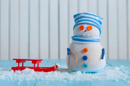 sledging people: Handmade snowman in striped cap with red sled on snow In winter. Christmas postcard background, empty space for text.
