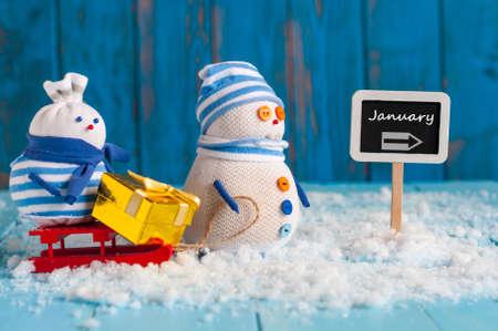 Word januari geschreven op richting ondertekenen en Sneeuwman met rode slee. Kerstmis, Nieuwjaar, winter decoraties