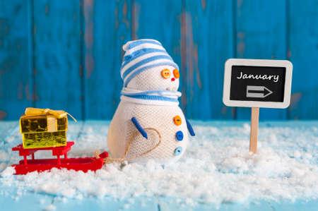 Word januari geschreven op richting ondertekenen en Sneeuwman met rode slee en nieuwe jaar cadeau. Decoratie van het Nieuwjaar