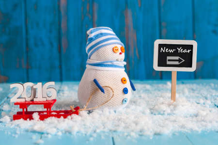 to go sledding: Christmas and new year concept. Handmade snowman with red sled And text 2016 near signpost With text New Year
