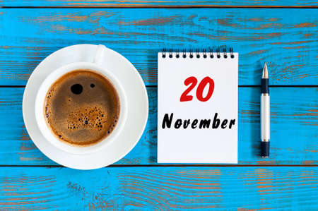 loose leaf: November 20th. Day 20 of month, loose-leaf calendar and white coffee cup at blue wooden workplace background. Autumn time, top view. Stock Photo