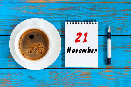 looseleaf: November 21st. Day 21 of month, morning drink cup with calendar on blue wooden workplace background. Autumn time. Empty space for text. Stock Photo