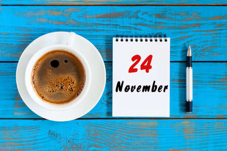November 24th. Day 24 of month, loose-leaf calendar and latte cup at blue wooden workplace background. Autumn time.