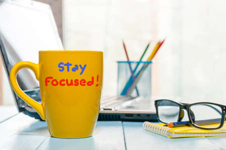 Stay focused - yellow morning cup of coffee, tea at home or office business workplace. Stock Photo