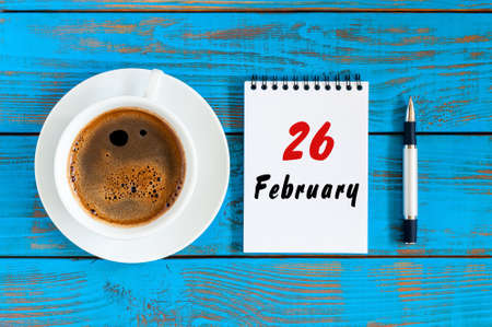recordar: February 26th. Day 26 of month, Top view on calendar and morning coffee cup at workplace background. Winter time