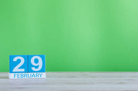 February 29th. Cube calendar for february 29 on wooden workplace with with green background and empty space For text. Leap year, intercalary day Stock Photo
