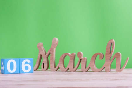March 6th. Day 6 of month, daily wooden calendar on table and green background. Spring time, empty space for text Stock Photo