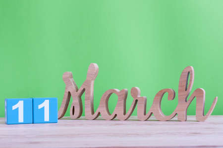 HI: March 11th. Day 11 of month, daily wooden calendar on table and green background. Spring day, empty space for text Stock Photo