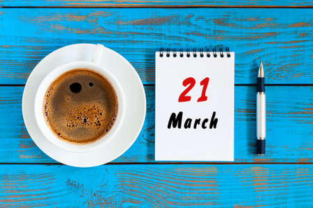March 21st. Day 21 of month, calendar on blue wooden table background with morning coffee cup. Spring time, Top view.