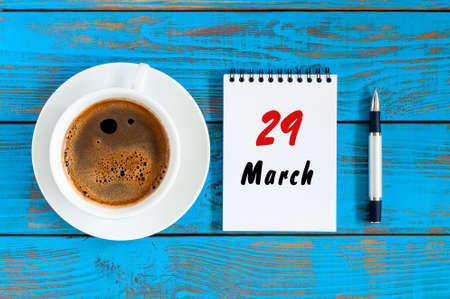 March 29th. Day 29 of month, calendar on blue wooden table background with morning coffee cup. Spring time, Top view. Stock Photo