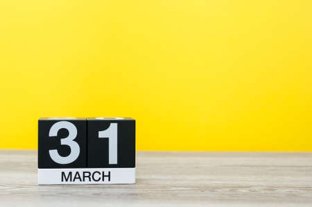 30 years old: March 31st. Day 31 of month, calendar on table with yellow background. Spring time, empty space for text