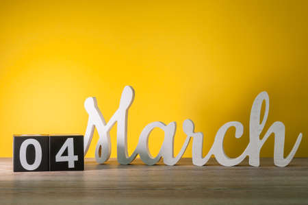 March 4th. Day 4 of month, daily wooden calendar on table with yellow background. Spring time, empty space for text