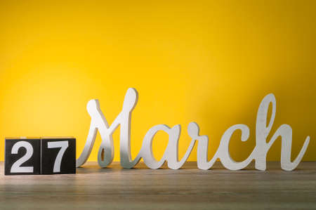 March 27th. Day 27 of month, daily wooden calendar on table with yellow background. Spring time, empty space for text. World Theatre Days Stock Photo