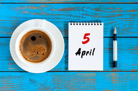 looseleaf: April 5th. Day 5 of month, loose-leaf calendar with morning coffee cup, at workplace. Spring time, Top view