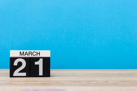 March 21st. Day 21 of month, calendar on table with blue background. Spring time, empty space for text
