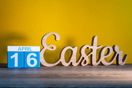 religion catolica: Easter 2017 - April 16th. Calendar and carved of wooden text Easter at yellow background. Holiday concept.