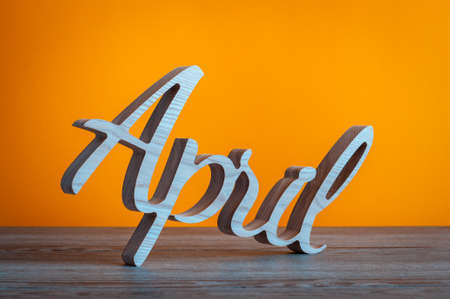 appointments: April word carved wood letters at orange background Stock Photo