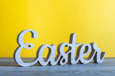 Easter - word carved of wood at yellow background. Holiday concept