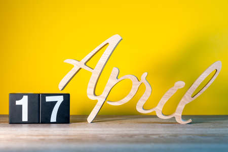 April 17th. Day 17 of month, calendar on wooden table and yellow background. Spring time, empty space for text