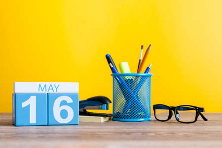 biographer: May 16th. Day 16 of month, calendar on business office table, workplace at yellow background. Spring time. Biographers Day