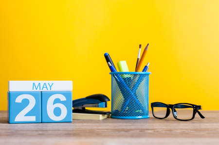 May 26th. Day 26 of month, calendar on business office table, workplace at yellow background. Spring time.