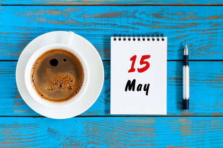 HI: May 15th. Day 15 of month, tear-off calendar with morning coffee cup at work place background. Spring time, Top view Stock Photo