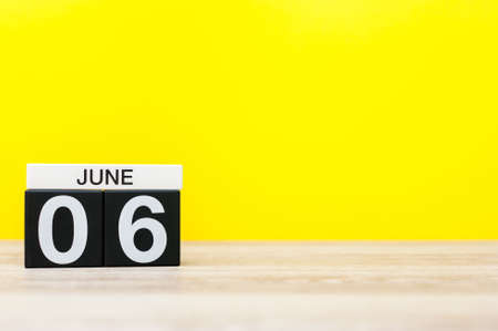 June 6th. Day 6 of month, calendar on yellow background. Summer day, empty space for text.