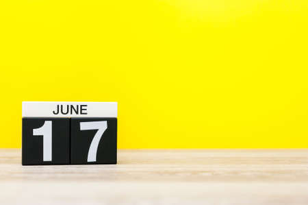 17th: June 17th. Day 17 of month, calendar on yellow background. Summer day. Empty space for text