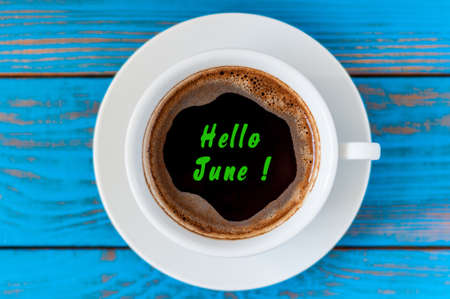 laying forward: Hello June text on morning cup of coffee at blue wooden background. Stock Photo