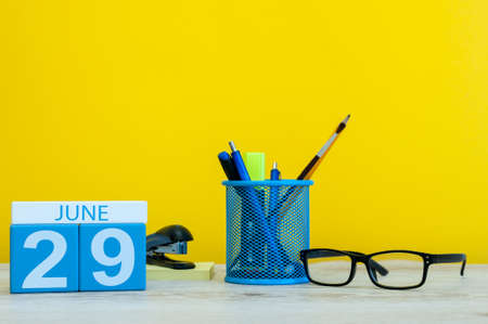 ninth: June 29th. Day 29 of month, calendar on yellow background with office suplies. Summer time at work Stock Photo