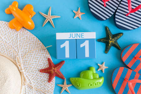 June 11th. Image of june 11 calendar on blue background with summer beach, traveler outfit and accessories. Summer day.
