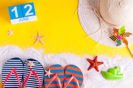 June 12th. Image of june 12 calendar on yellow sandy background with summer beach, traveler outfit and accessories. Summertime concept