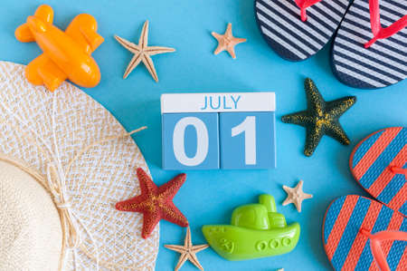 first day: July 1st. Image of july 1 calendar with summer beach accessories and traveler outfit on background. Summer day, Vacation concept Stock Photo