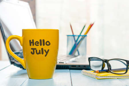 Hello July - inscription at yellow morning coffee or tea cup at business office background. Summer month, Calendar concept.