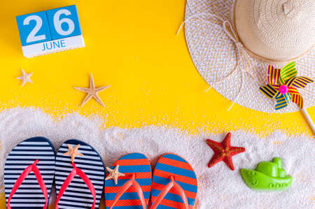 first day: June 26th. Image of june 26 calendar on yellow sandy background with summer beach, traveler outfit and accessories. Summertime concept Stock Photo