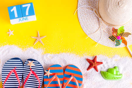 17th: June 17th. Image of june 17 calendar on yellow sandy background with summer beach, traveler outfit and accessories. Summertime concept Stock Photo