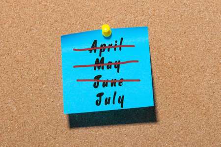 first day: July beginning concept. Sticker with crossed out months April, May and June. Message at business corkboard.
