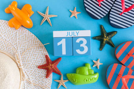 July 13th. Image of july 13 calendar with summer beach accessories and traveler outfit on background. Summer day, Vacation concept