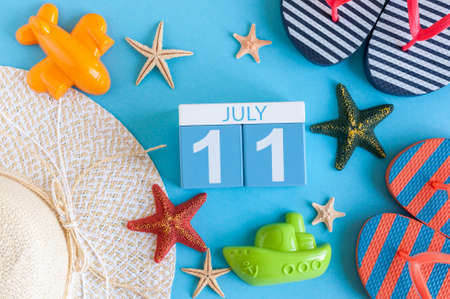 11th: July 11th. Image of july 11 calendar with summer beach accessories and traveler outfit on background. Summer day, Vacation concept Stock Photo
