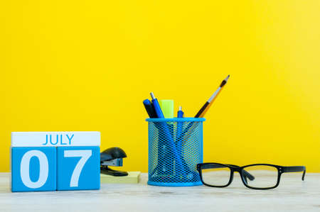 July 7th. Image of july 7, calendar on yellow background with office supplies. Summer time. With empty space for text