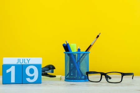 July 19th. Image of july 19, calendar on yellow background with office supplies. Summer time. With empty space for text.