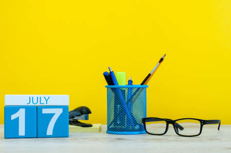 first day: July 17th. Image of july 17, calendar on yellow background with office supplies. Summer time. With empty space for text. Stock Photo