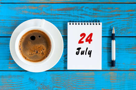 24: July 24th. Day 24 of month, calendar on blue wooden table background with morning coffee cup. Summer concept Stock Photo