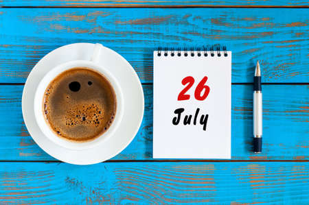 event planning: July 26th. Day 26 of month, calendar on blue wooden table background with morning coffee cup. Summer concept