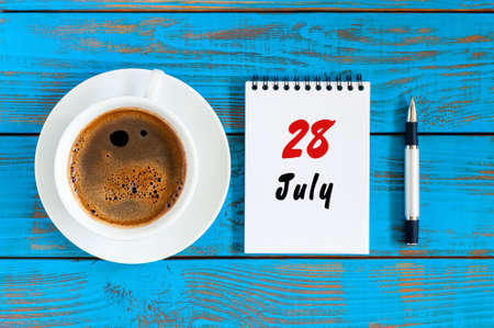 July 28th. Day 28 of month, calendar on blue wooden table background with morning coffee cup. Summer concept Stock Photo