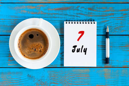 July 7th. Day 7 of month, calendar on blue wooden table background with morning coffee cup. Summer concept Stock Photo