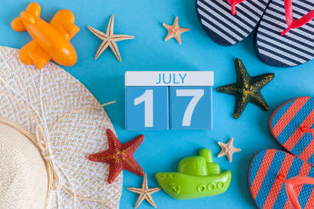 17th: July 17th. Image of july 17 calendar with summer beach accessories and traveler outfit on background. Summer day, Vacation concept