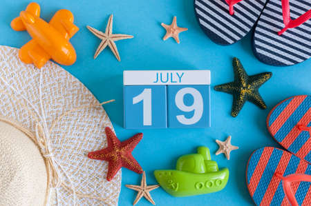 July 19th. Image of july 19 calendar with summer beach accessories and traveler outfit on background. Summer day, Vacation concept Stock Photo